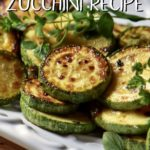 Yellow and green sauteed zucchini on a white dish.