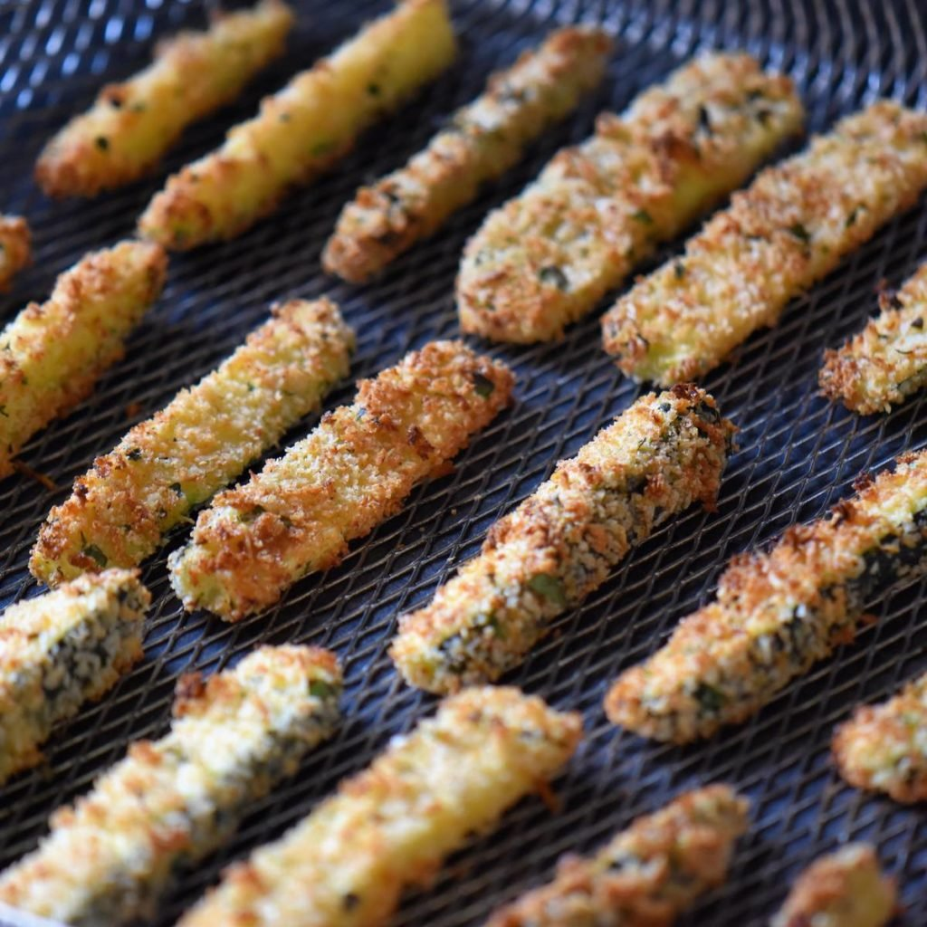 Baked zucchini fries on an air fryer basket.