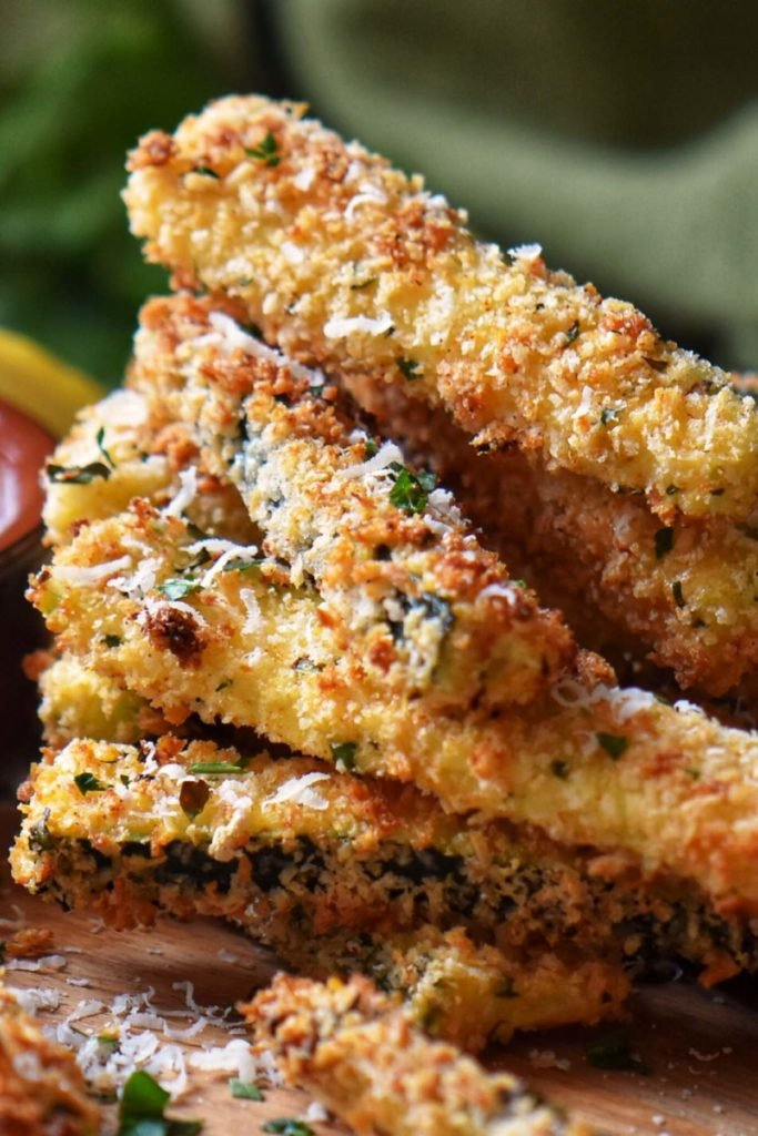 A stack of Air Fryer Parmesan encrusted Zucchini Sticks on a wooden board.