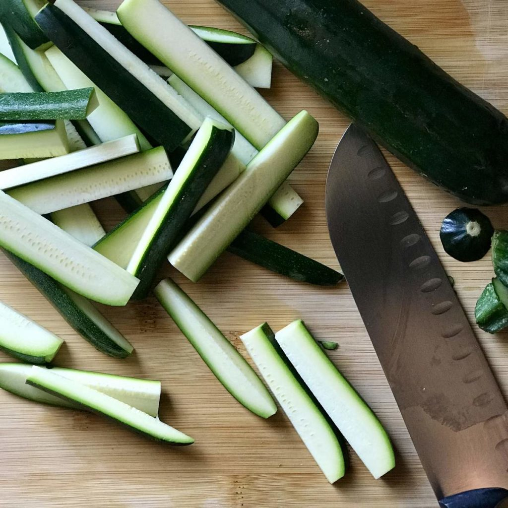 Sliced courgette on a wooden board.