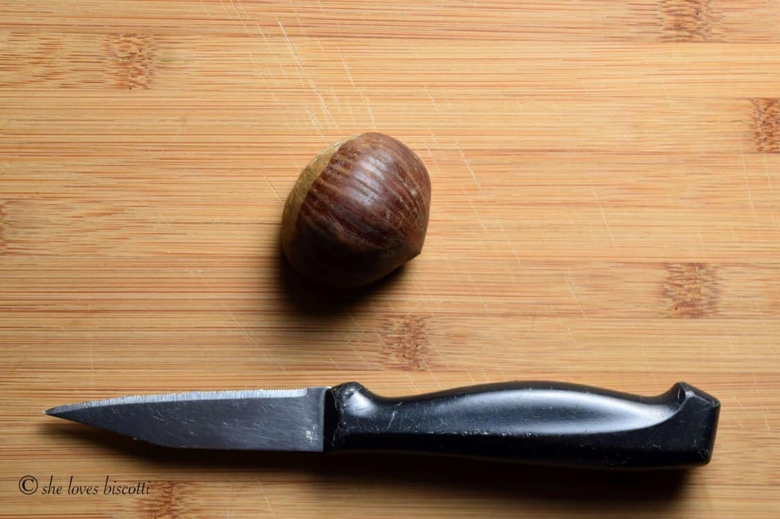 An overhead shot of a small knife with a black handle and a chestnut on a wooden cutting board.