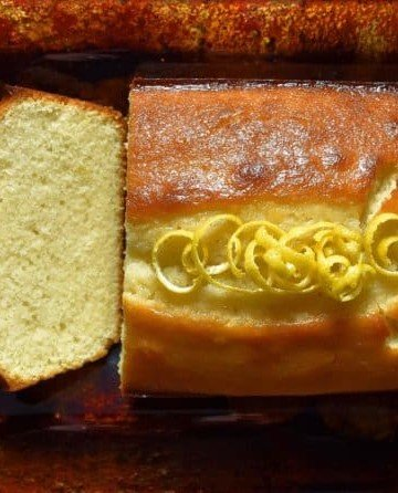 A few pieces of Extra Moist Lemony Lemon Loaf are sliced on a platter.