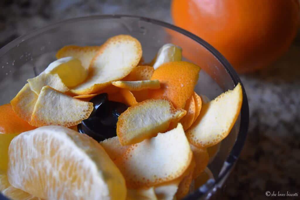 A whole orange in a food processor.