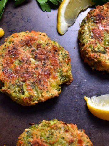 Broccoli fritters surrounded by lemon wedges.