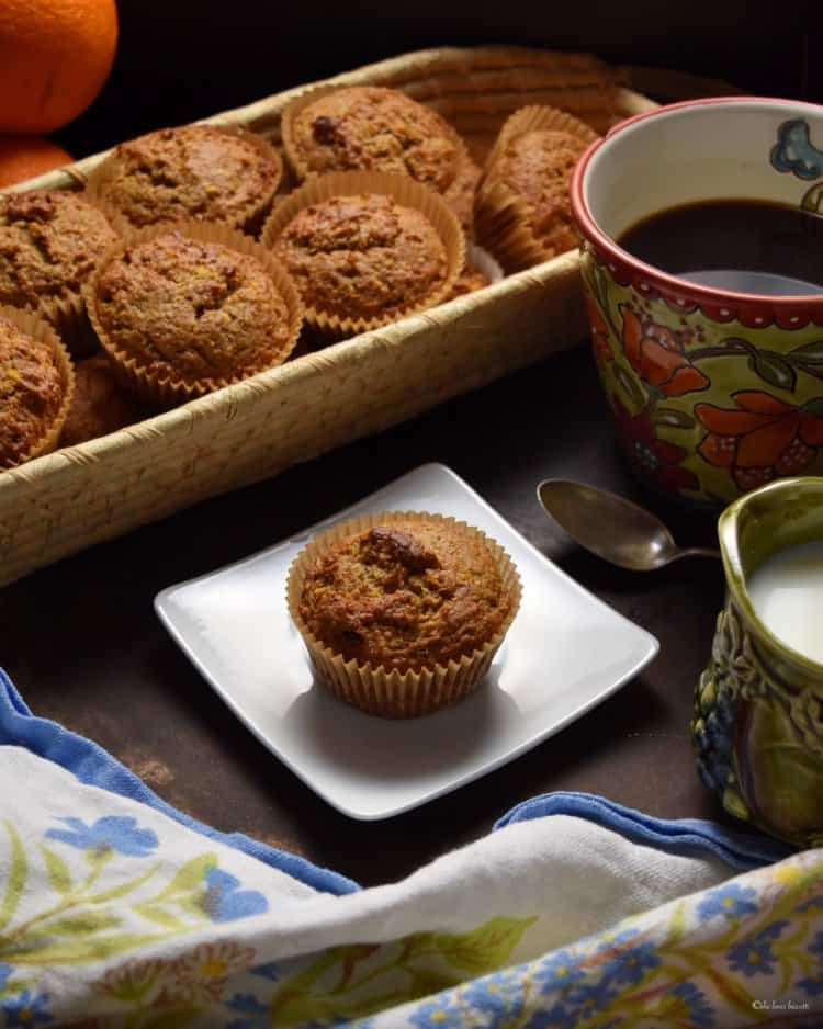 A basket of orange date muffins next to a cup of coffee.