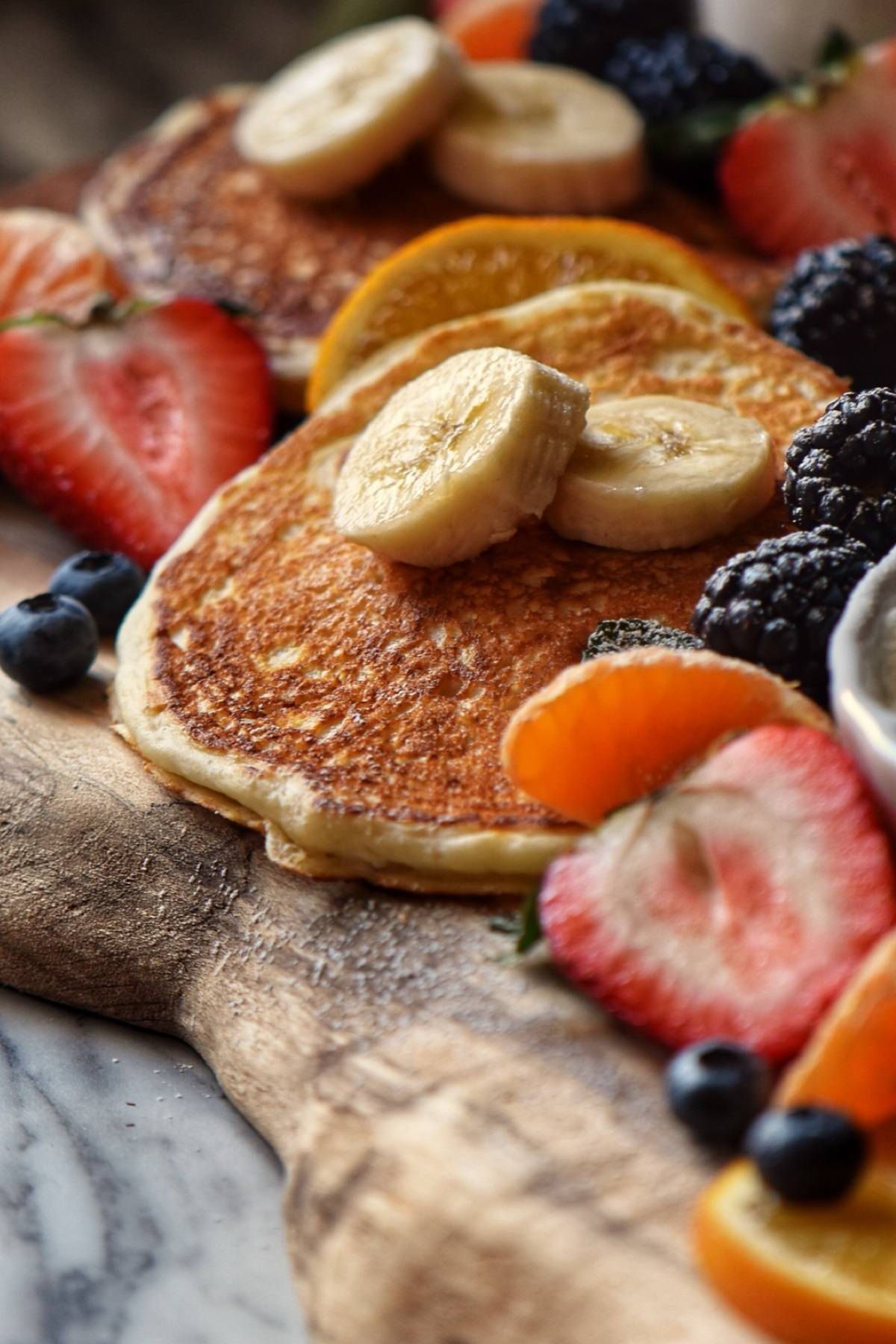 Buttermilk Pancakes surrounded with fresh fruit on a wooden board.