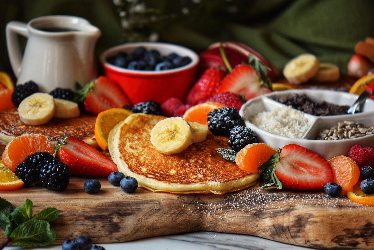 A pancake platter filled with fluffy pancakes, fruit and other toppings.