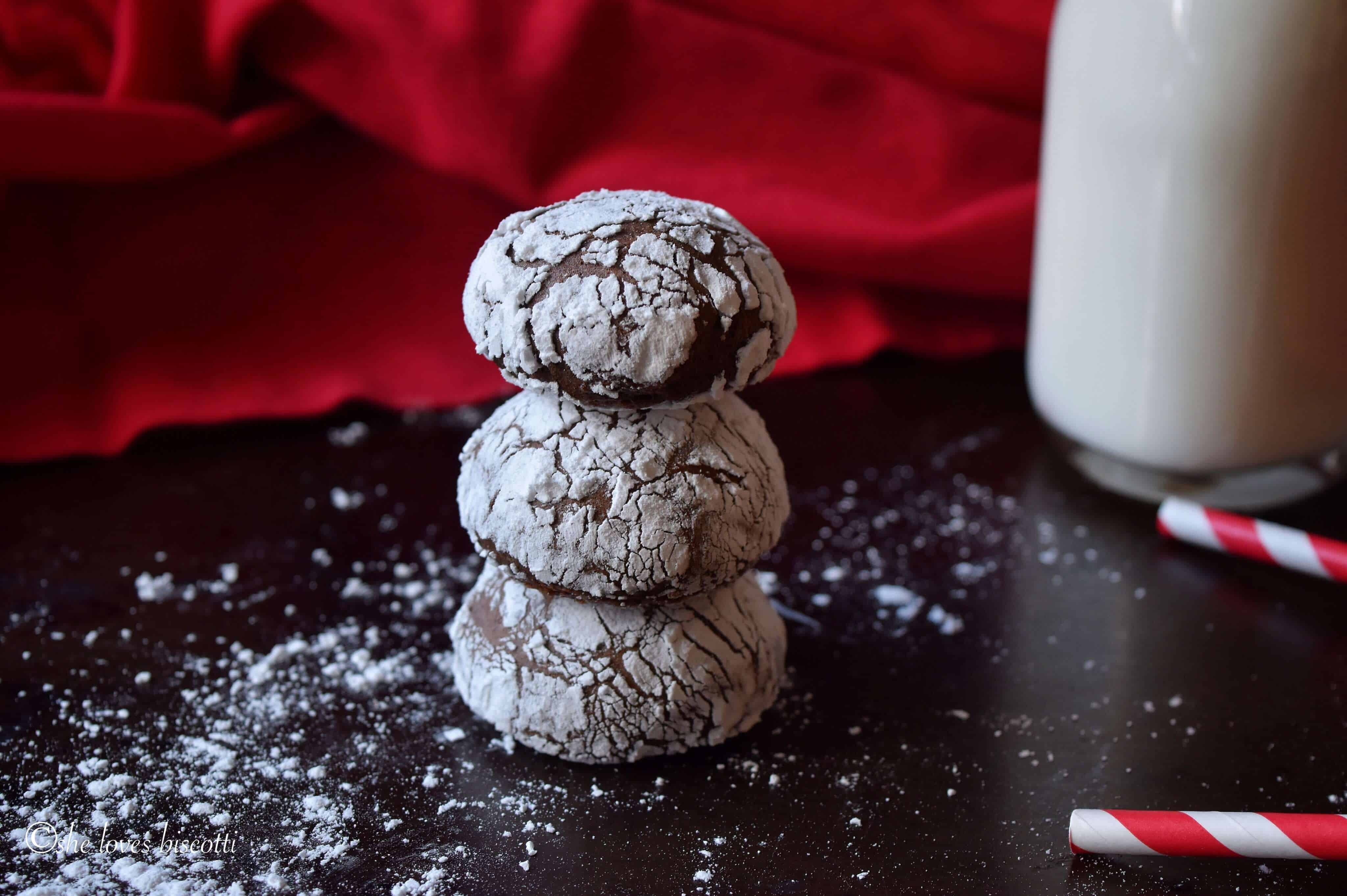 A stack of three Italian Chocolate Cookies with a bottle of milk in the background.
