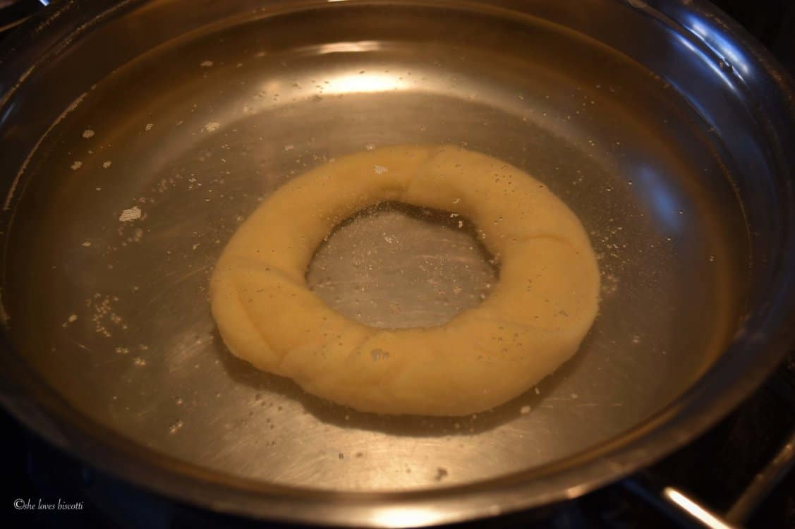 A pot of water with one taralli being boiled.