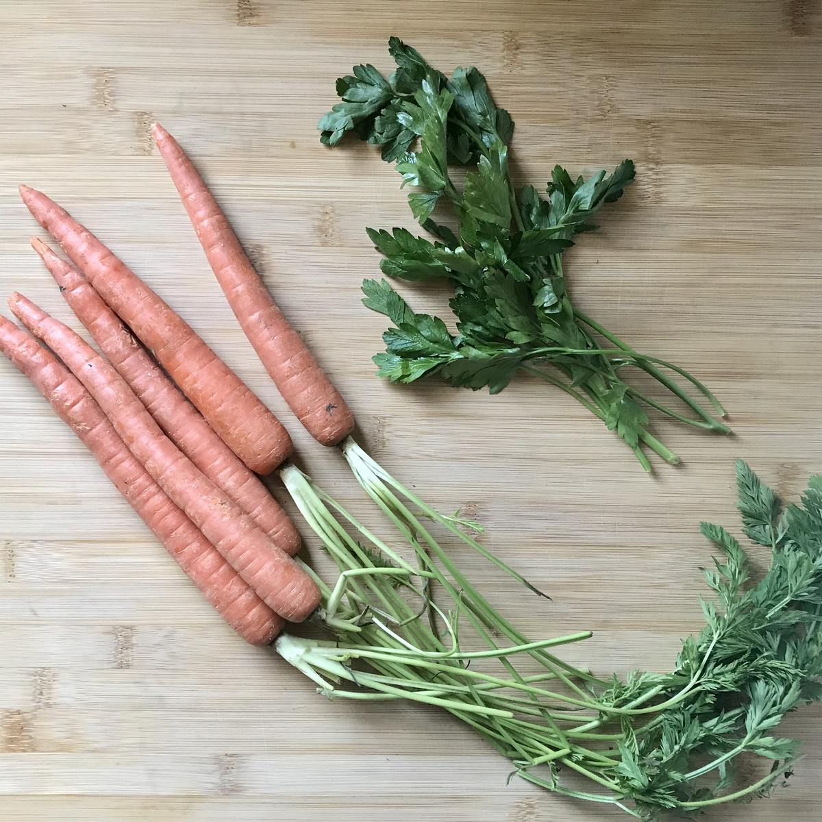 A bunch of carrots and parsley on a wooden board.