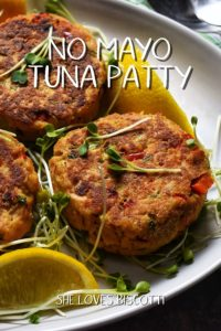 Tuna Patties on a white oval plate topped with micro greens and surrounded by lemon wedges.