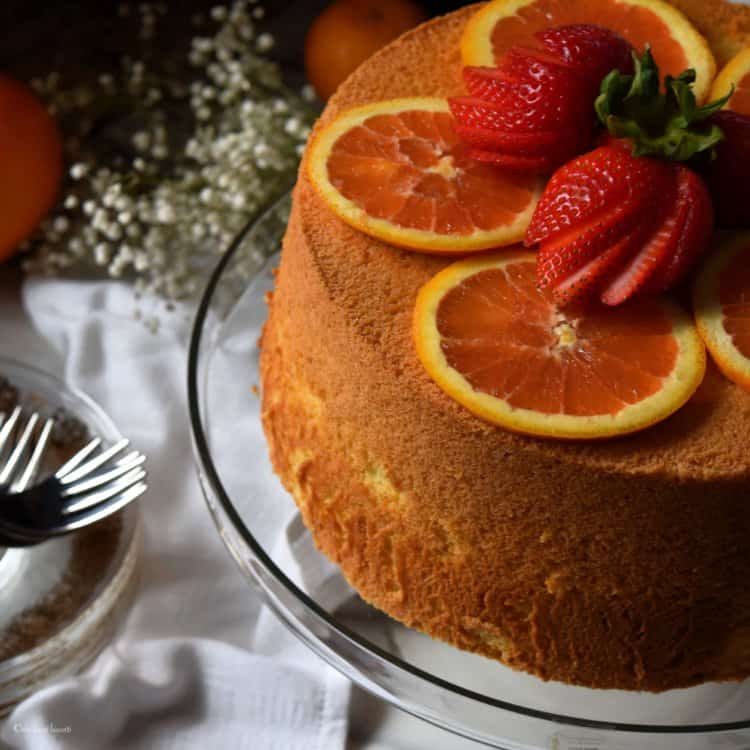 Strawberries and orange slices atop a cake.