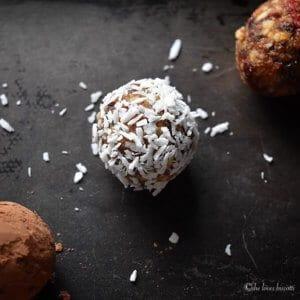 A single Greek Yogurt Goji Berry Almond Date Energy Bite covered in coconut.