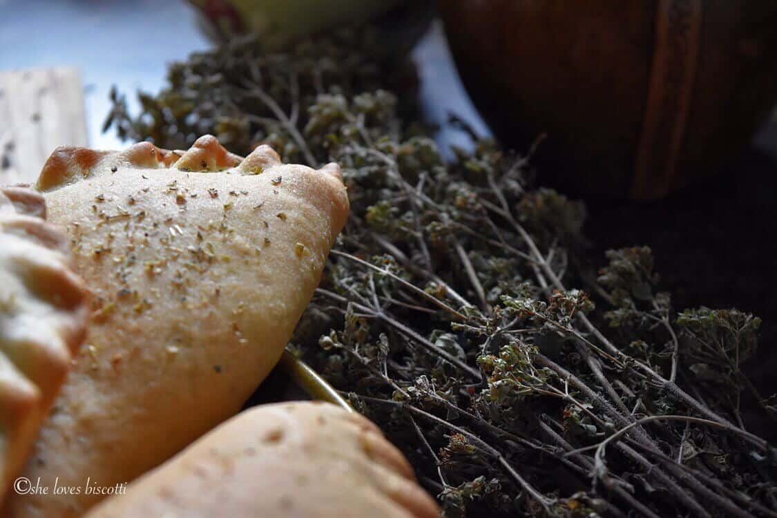 Stems of dried oregano next to calzones.