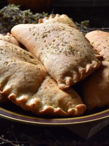 A pile of calzones on a plate.