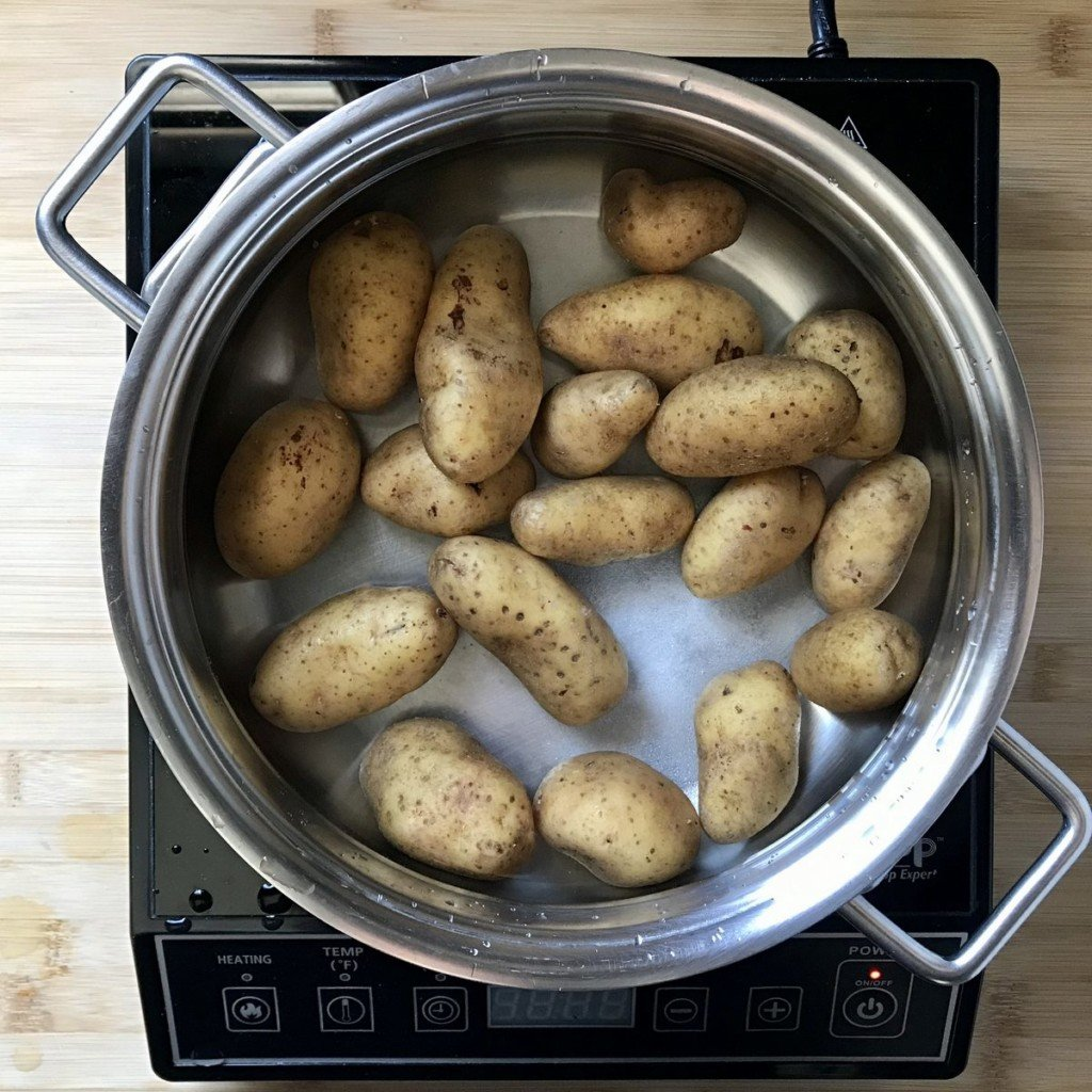 Fingerling potatoes in a pot of water, about to be boiled.