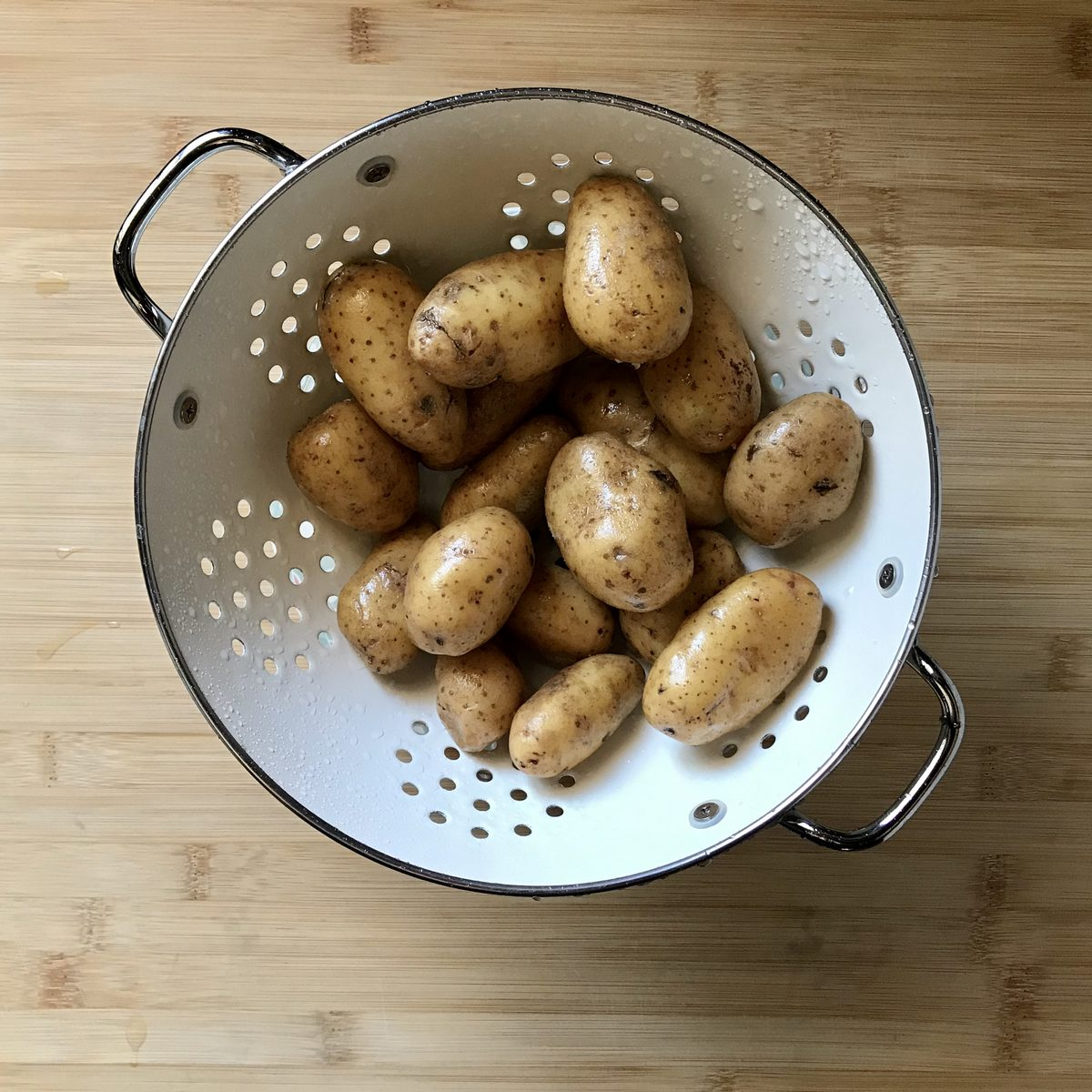 Creamer potatoes in a white colander.