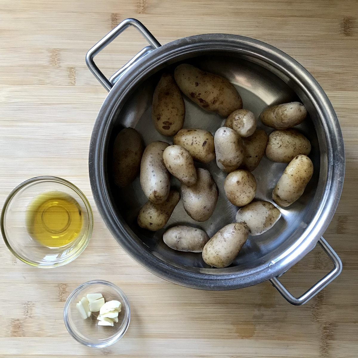 Boiled and drained fingerling potatoes in a pot, next to olive oil and garlic.