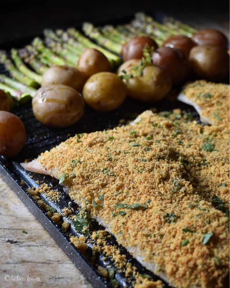A sheet pan with the cod fish, potatoes and asparagus ready to be baked.