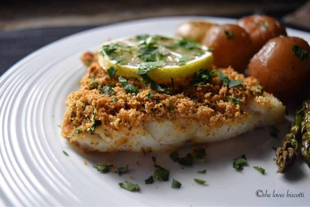 A fish fillet with seasoned breadcrumbs on a white plate.