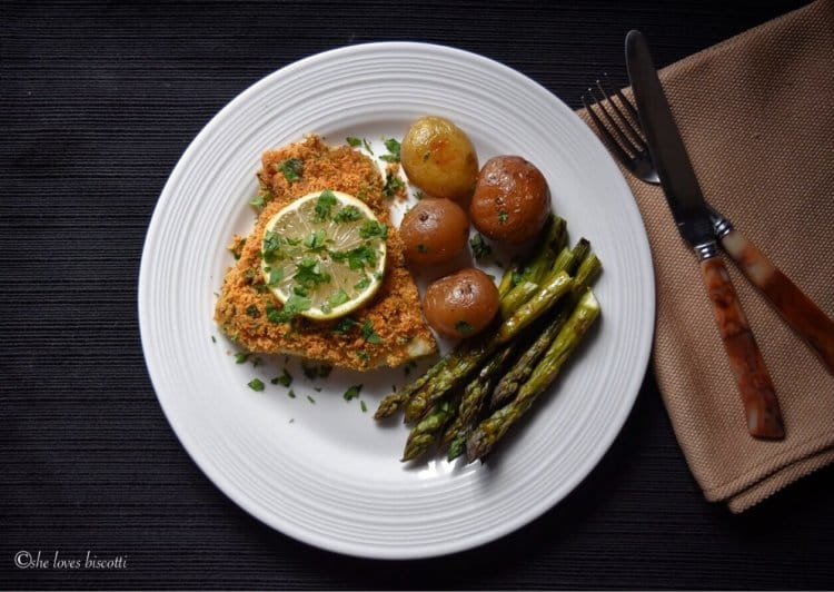 An overhead shot of a plate of baked cod fish, potatoes and asparagus.