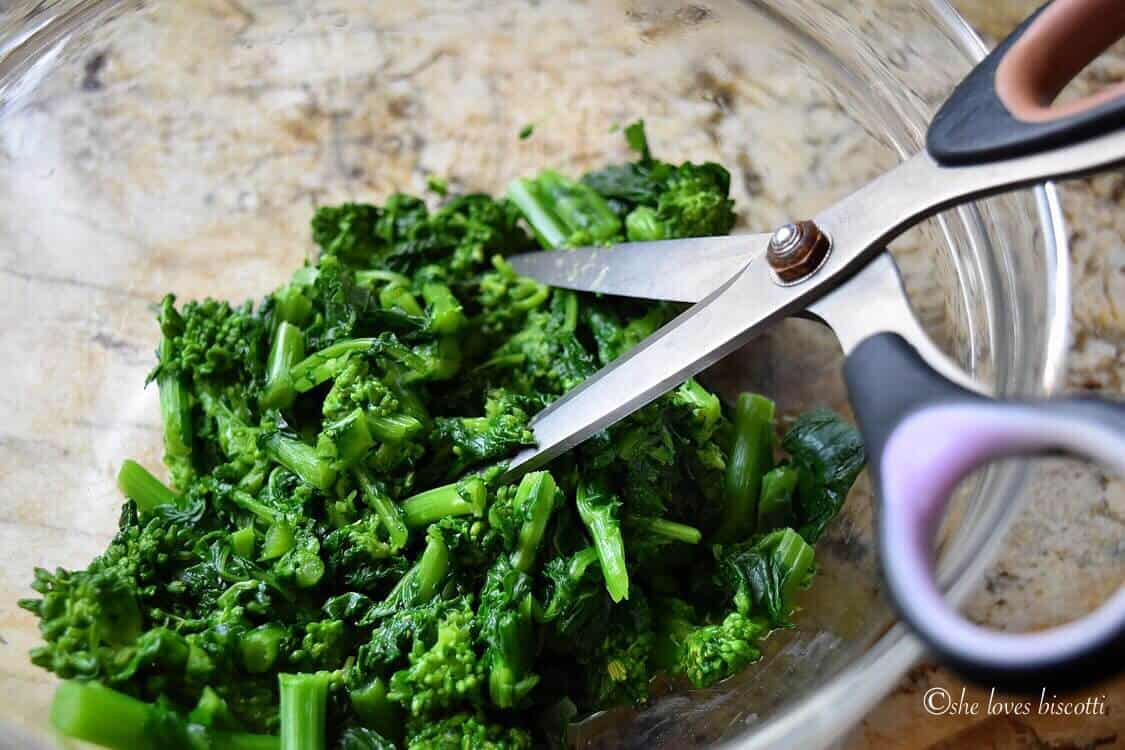 Scissors are used to cut the broccoli rabe.