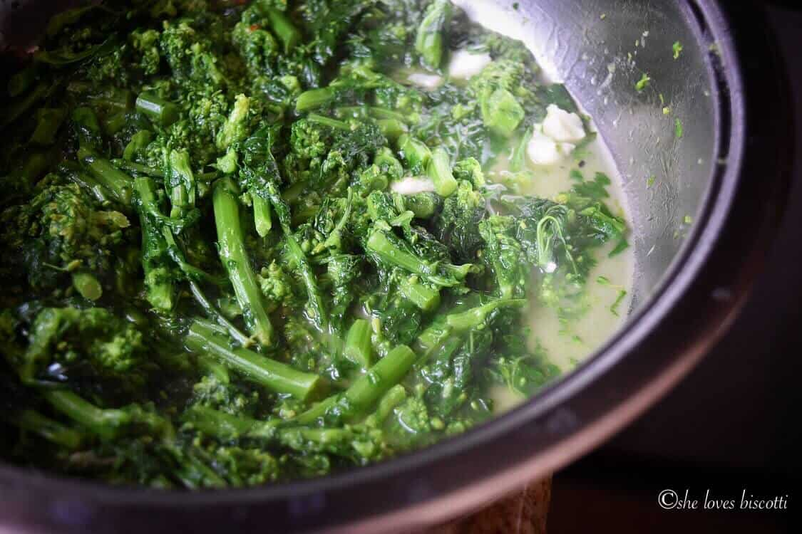 Pan of broccoli rabe is being cooked.