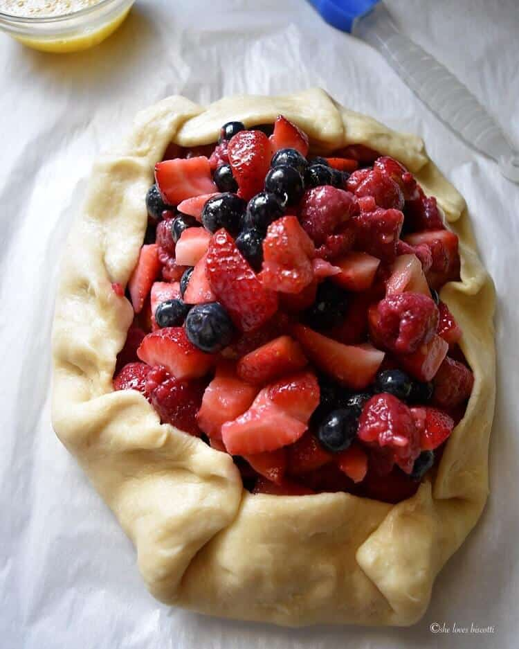 The crostata dough has been crimped and is enclosing a pile of fresh berries.