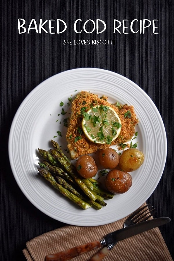An overhead shot of baked cod fish with a side of potatoes and asparagus on a white plate.