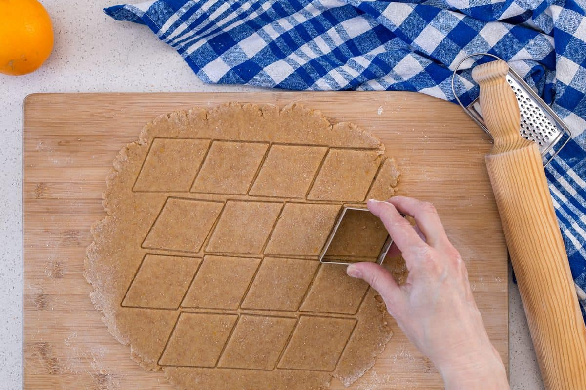 A cookie cutter is being used to cut out shapes from the rolled out dough.
