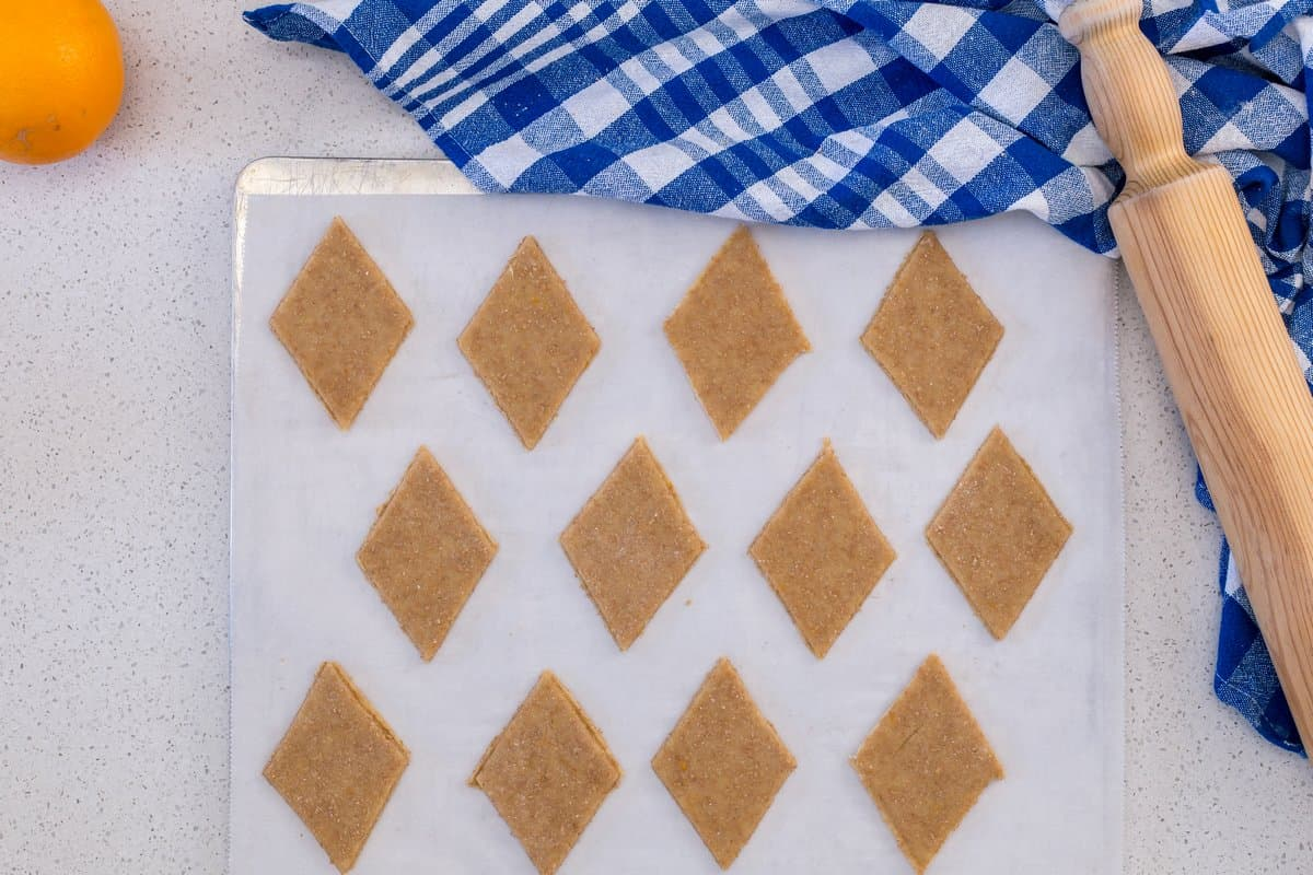 The cut out shapes are placed on a parchment lined cookie tray.