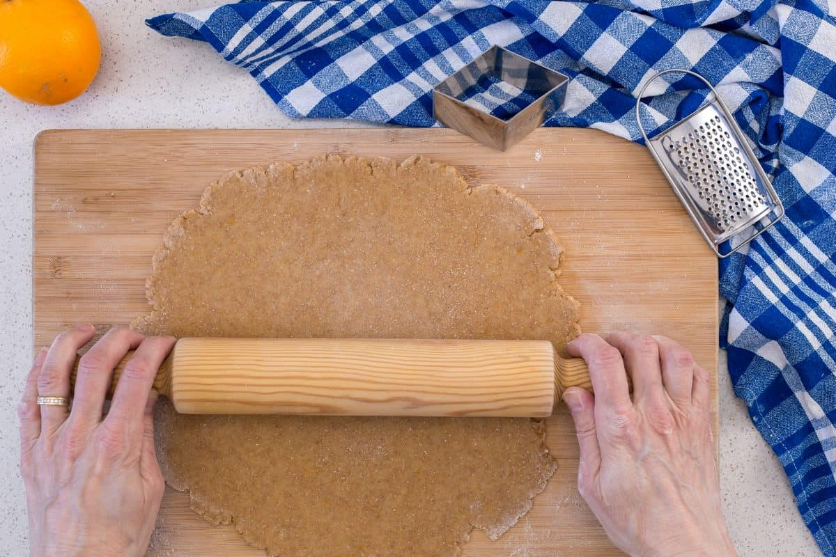 The ball of dough is being rolled out to make whole wheat cookies.