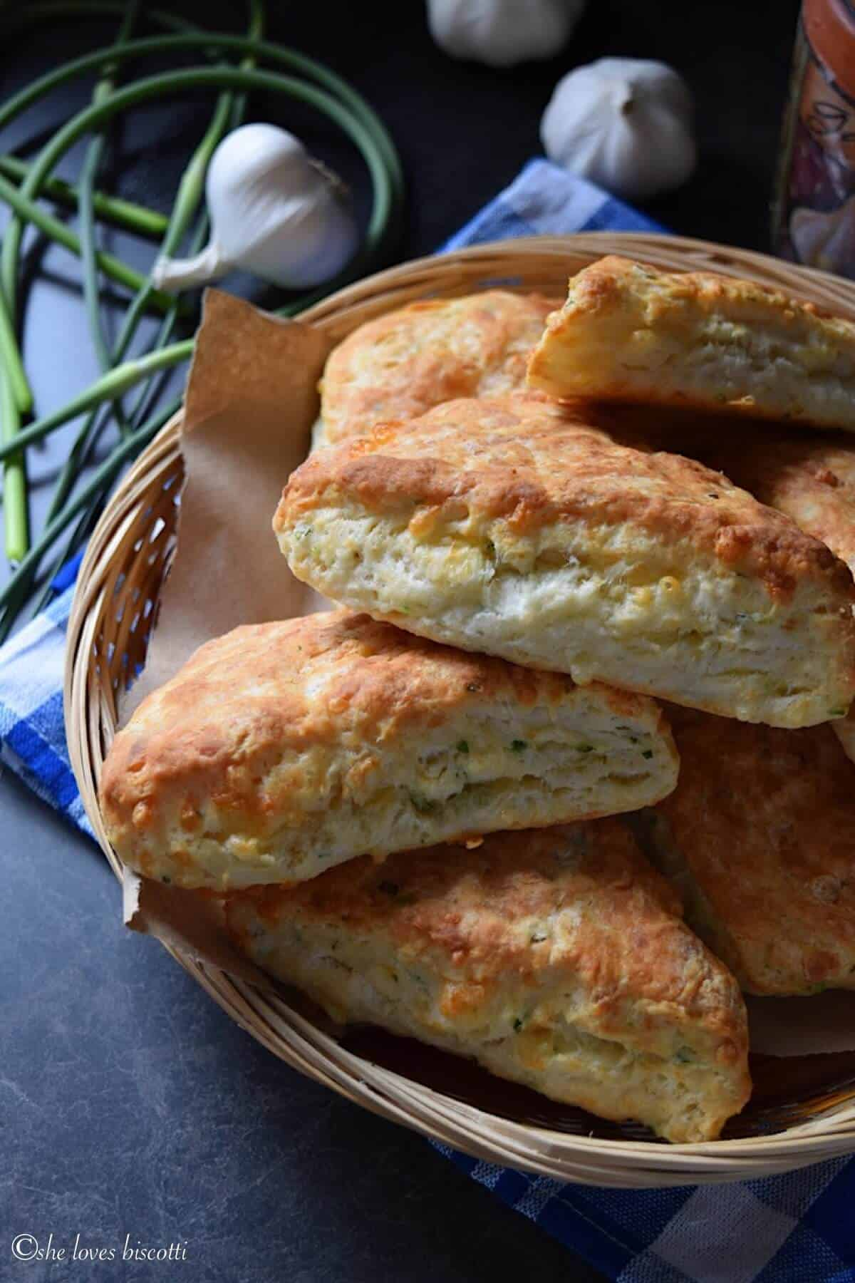 Cheddar Biscuits made with garlic scapes in a wicker basket.