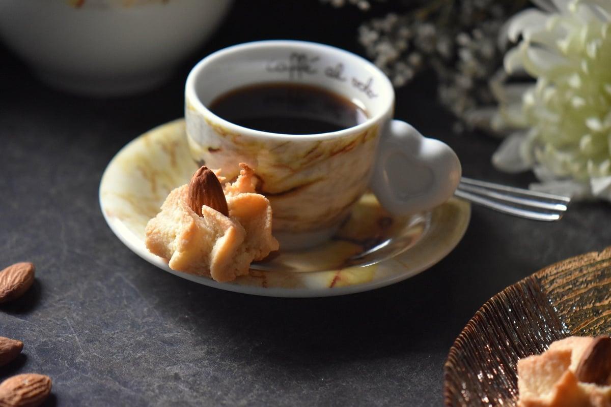 """A single amaretti cookie next to a """"caffe al volo thun"""" espresso cup."""