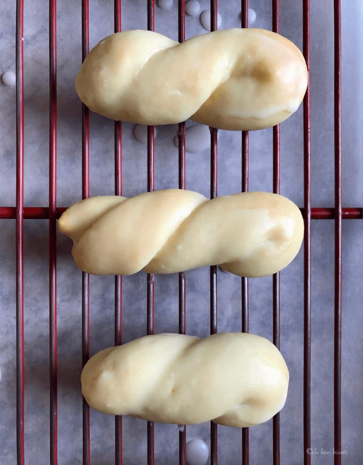 3 glazed lemon cookies on a cookie rack.