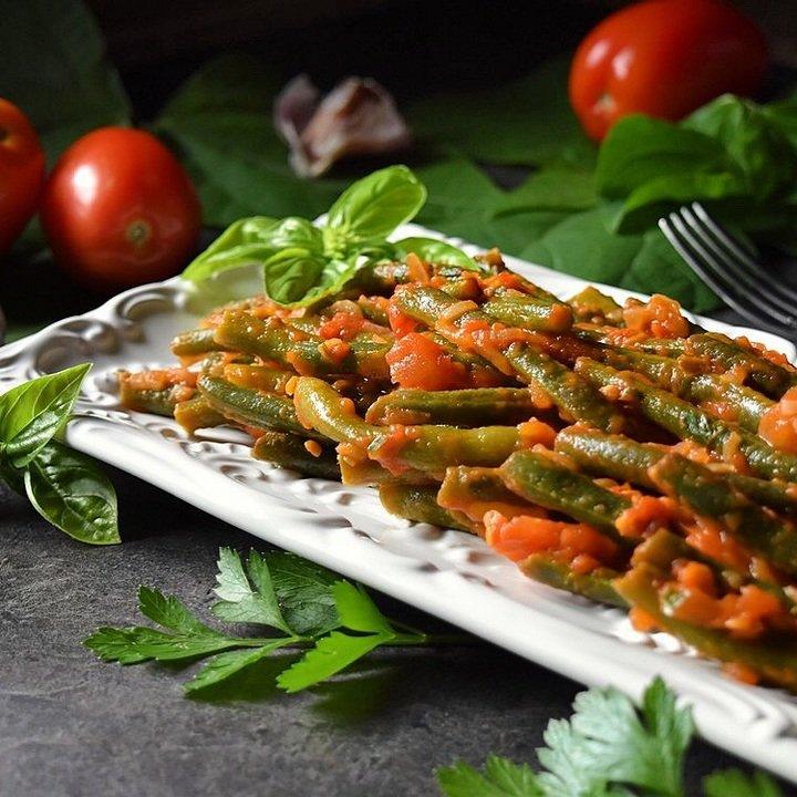 The completed dish of Italian Green Beans is plated on a white serving dish.
