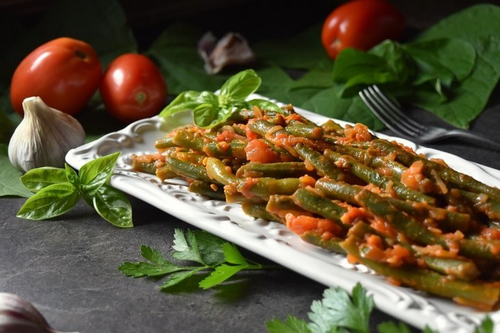 Green Beans with Tomatoes on a white ceramic dish surrounded by fresh tomatoes and garlic.