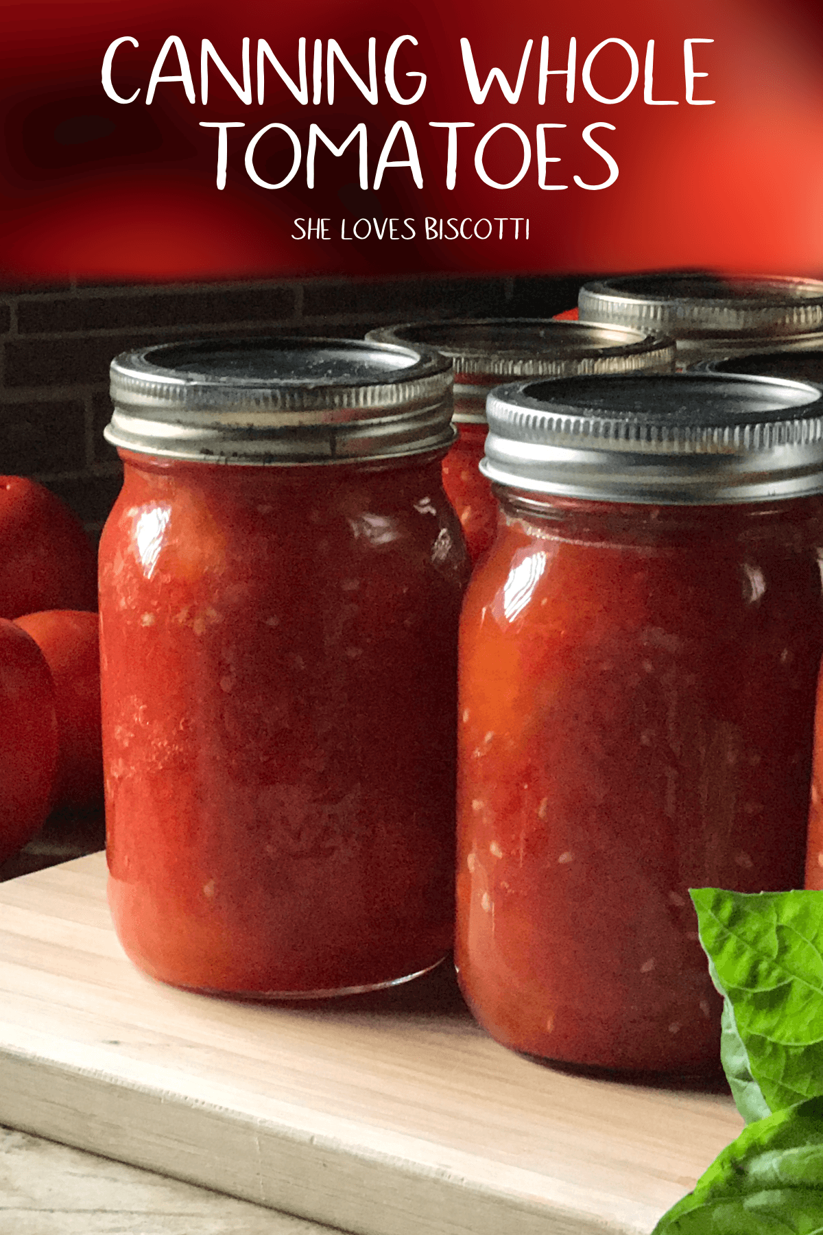 A few jars of canned whole tomatoes on a wooden board.