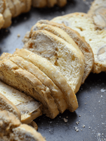 A few Thin Crispy Almond Biscotti di Nunzia are shown stacked closely together.