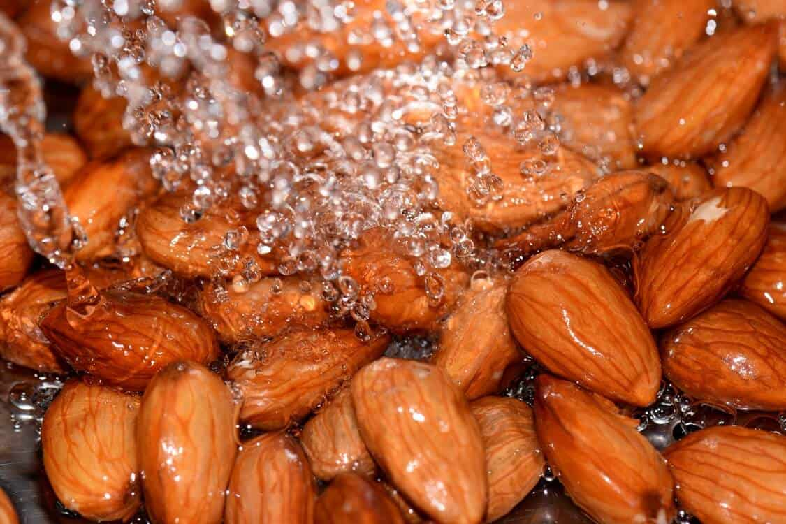 Almonds being rinsed under running water.
