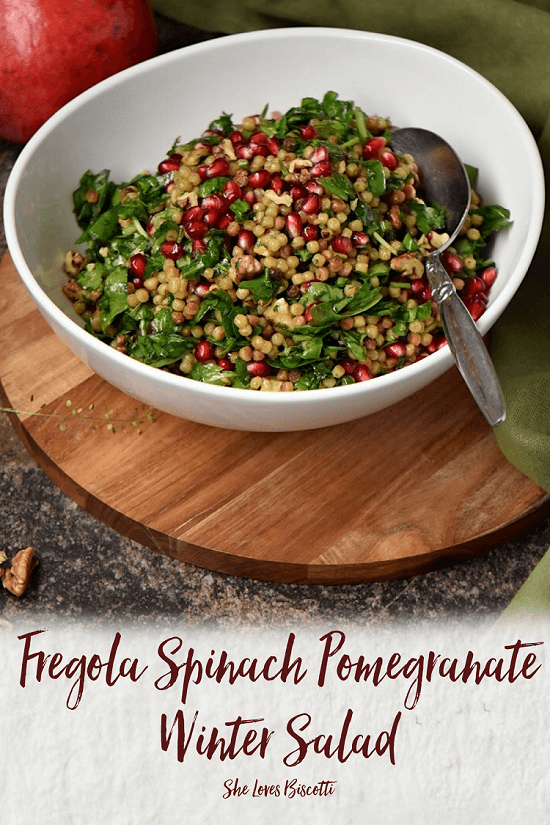 A white bowl filled with the Fregola Spinach and Pomegranate Winter Salad