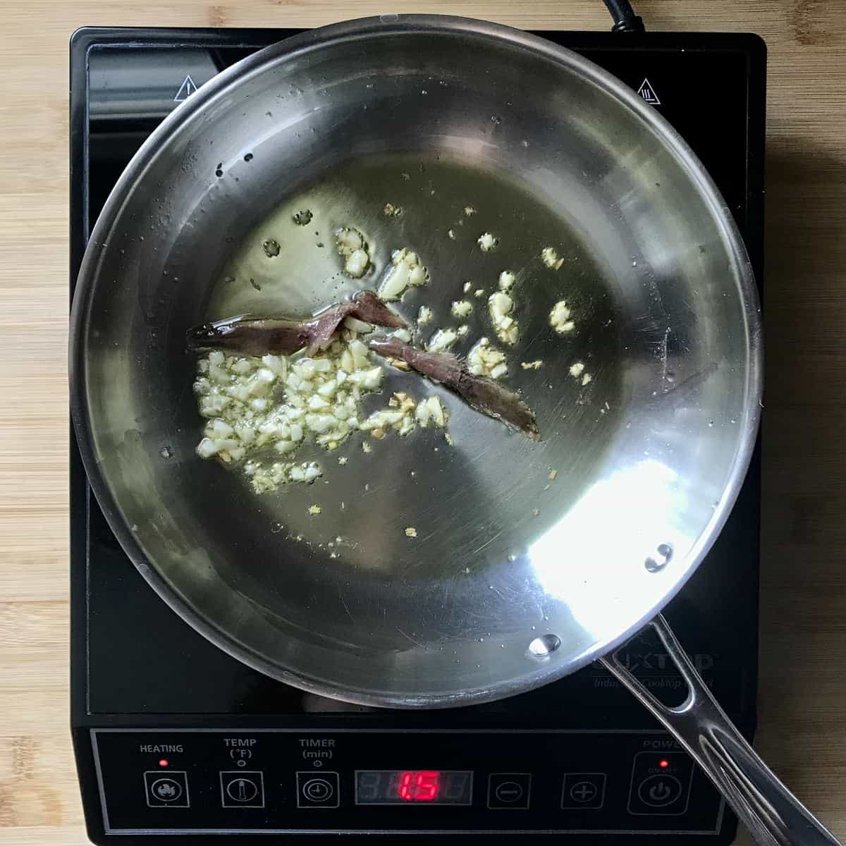 Chopped garlic and anchovies being sauteed in a saucepan.