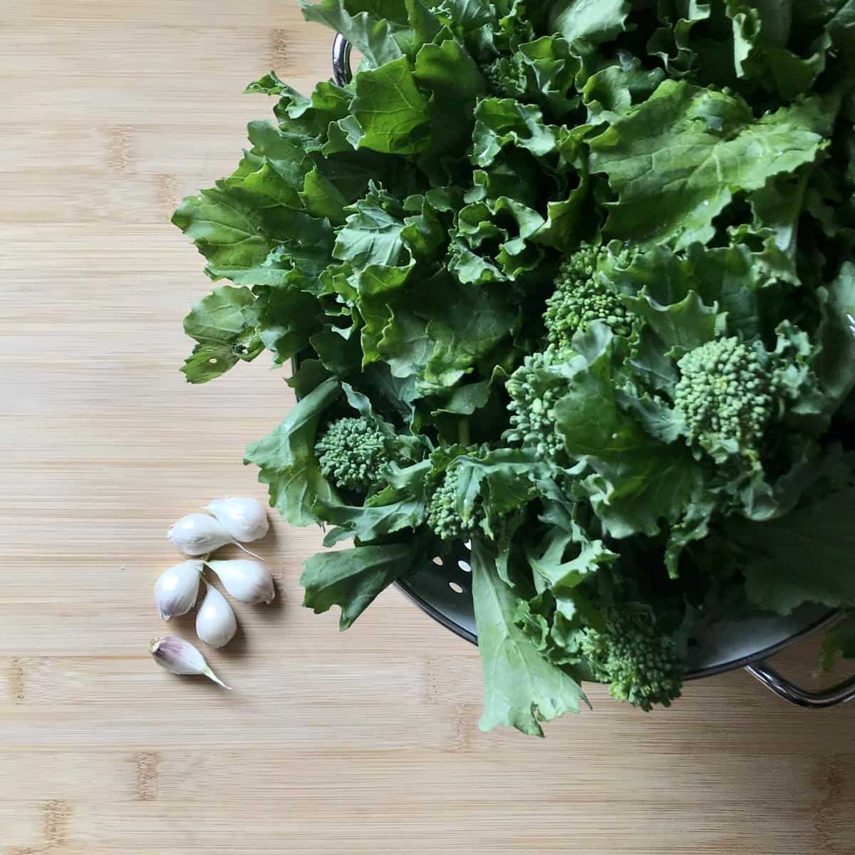 Garlic cloves and broccoli rabe on a wooden board.