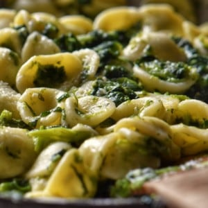 Orecchiette pasta with broccoli rabe tossed in a pan.