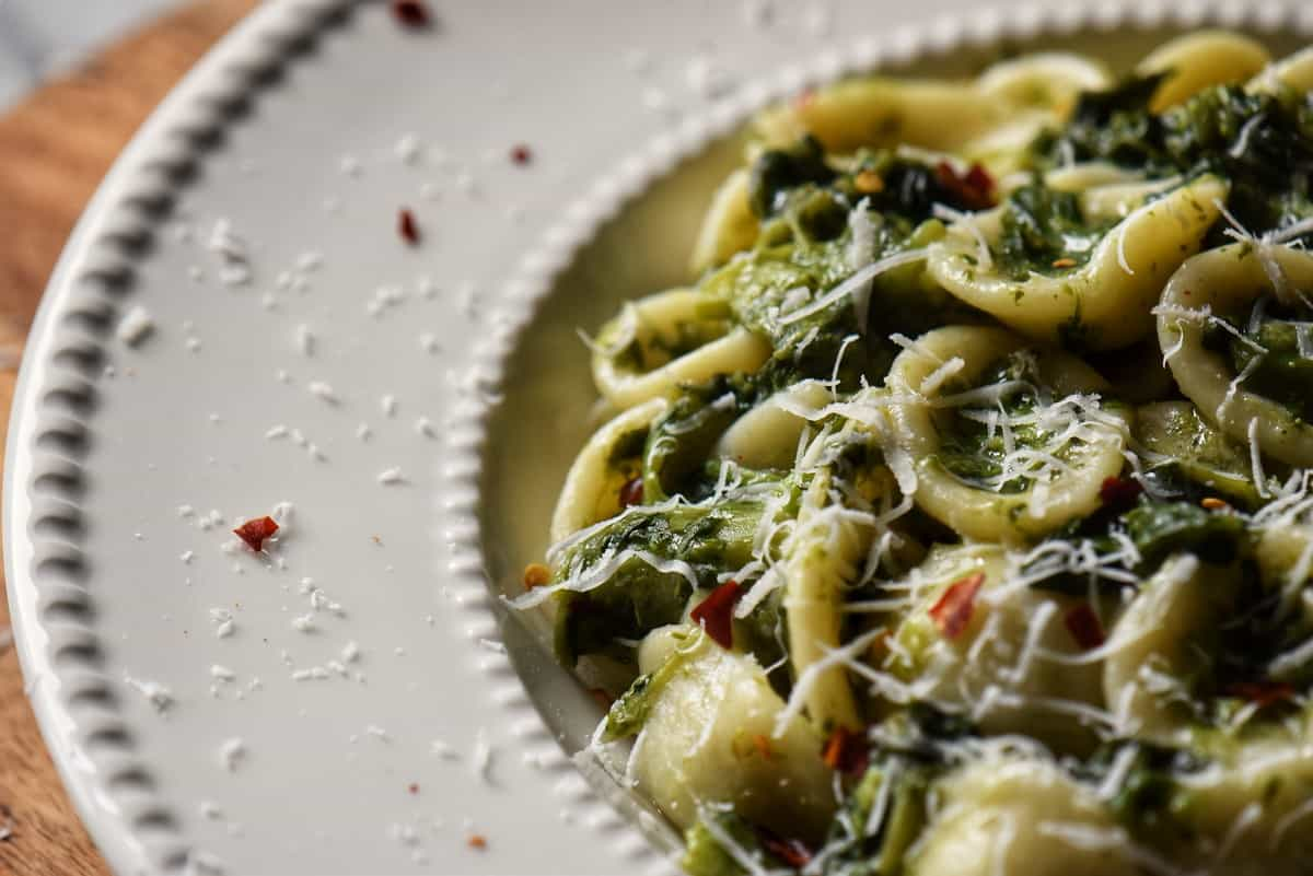 Grated cheese garnishes a plate of broccoli rabe pasta.