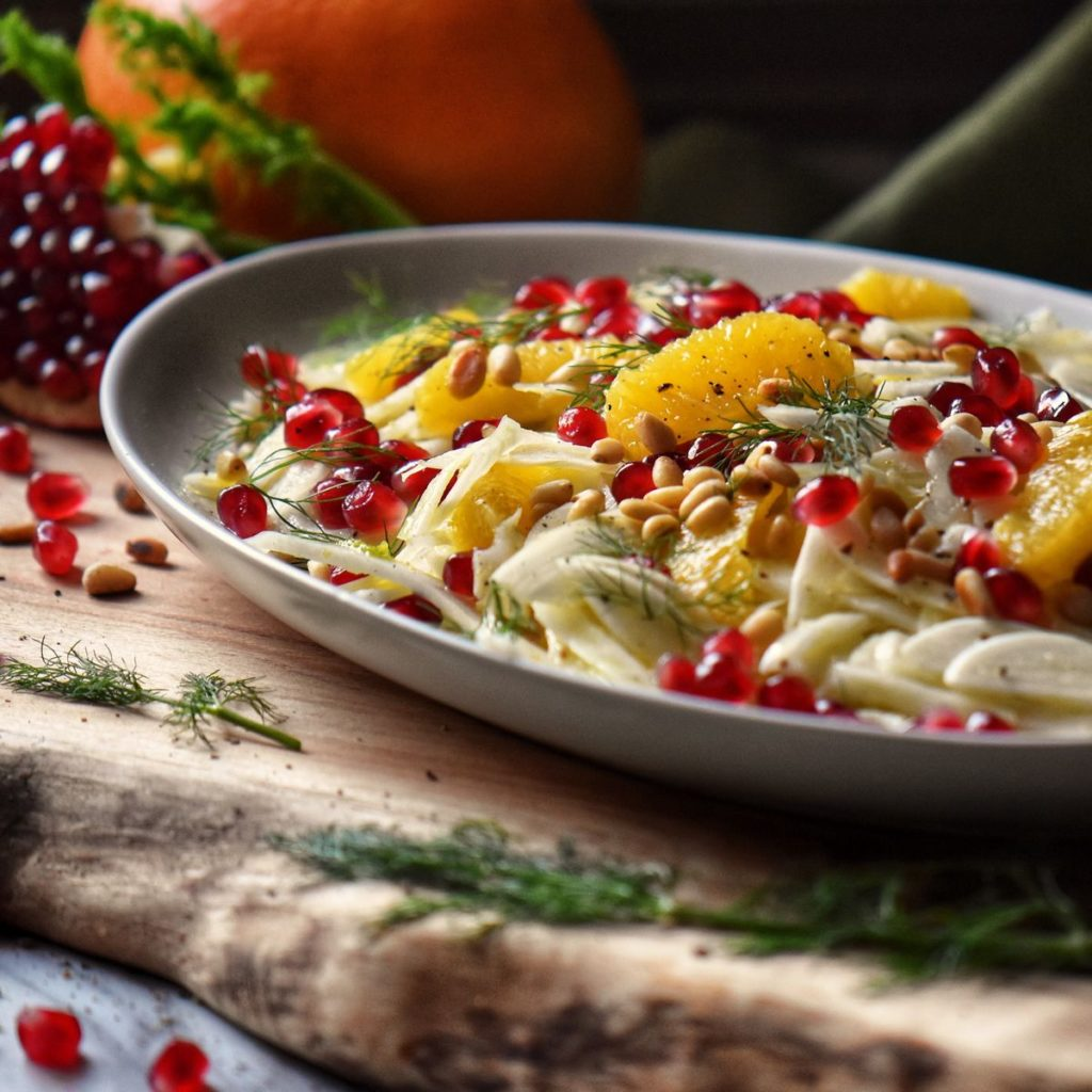 Pomegranate arils, orange sections and thinly sliced fennel in a serving platter.