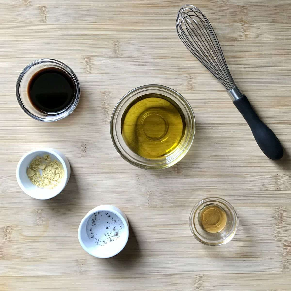 The ingredients to make the balsamic vinaigrette on a wooden table.