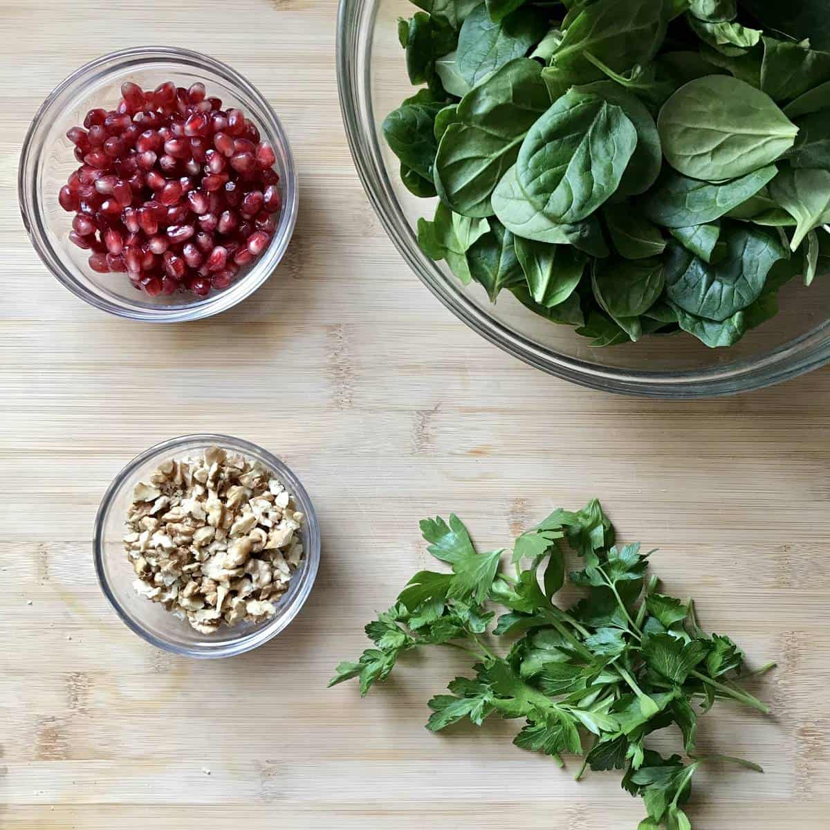 Spinach, parsley, walnuts and pomegrante arils on a wooden board.