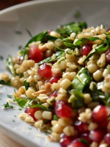 A colorful bowl of the Simple Fregola Spinach Pomegranate Winter Salad is shown.