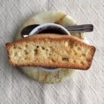 Single anise biscotti set over an espresso cup of coffee.